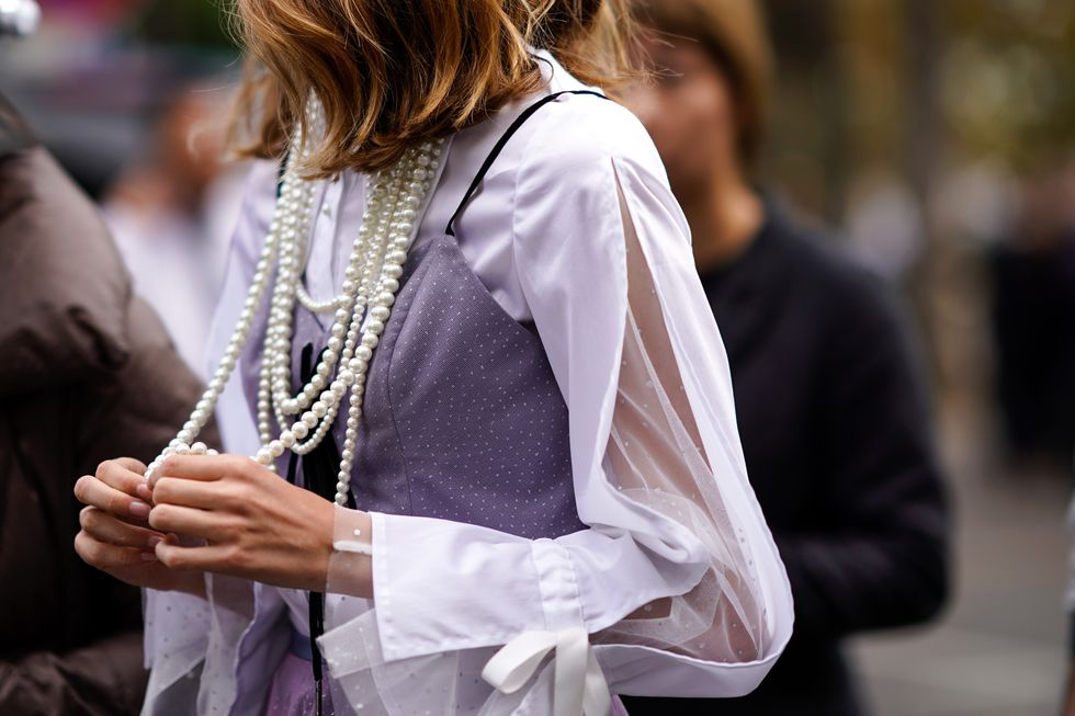 guest-wears-a-pearl-necklace-a-pink-lace-dress-outside-news-photo-1047173526-1544458354